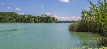 Bello lago Wörthsee con l'isola Wörth preso da un pilastro Paesaggio verde con il cottage, la canna e le piante acquatiche su u fotografia stock libera da diritti