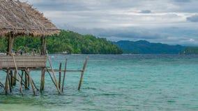 Bello Lagoone blu con alcune capanne di bambù, alloggio presso famiglie di Kordiris, Palmtree nella parte anteriore, Gam Island,  Immagini Stock