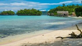 Bello Lagoone blu con alcune capanne di bambù, alloggio presso famiglie di Kordiris, Palmtree nella parte anteriore, Gam Island,  Immagini Stock Libere da Diritti