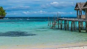 Bello Lagoone blu con alcune capanne di bambù, alloggio presso famiglie di Kordiris, Palmtree nella parte anteriore, Gam Island,  Fotografia Stock
