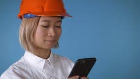 Bello lavoratore in uniforme che manda un sms sul cellulare archivi video