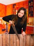 Bello legno di taglio della giovane donna con una sega Fotografia Stock Libera da Diritti