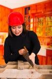 Bello legno di taglio della giovane donna con una sega Immagine Stock Libera da Diritti