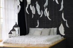 Bello letto vicino ad una grande finestra e con le piume sul soffitto fotografia stock
