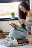 Bello lettore del libro elettronico della lettura della giovane donna a casa Fotografia Stock Libera da Diritti