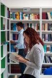 Bello libro della tenuta della ragazza dello studente della testarossa nella biblioteca con Fotografie Stock