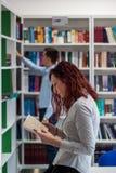 Bello libro della tenuta della ragazza dello studente della testarossa nella biblioteca con Fotografie Stock Libere da Diritti