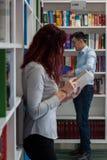 Bello libro della tenuta della ragazza dello studente della testarossa nella biblioteca con Immagini Stock