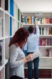 Bello libro della tenuta della ragazza dello studente della testarossa nella biblioteca con Immagine Stock