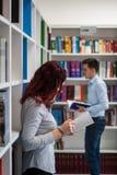 Bello libro della tenuta della ragazza dello studente della testarossa nella biblioteca con Immagine Stock Libera da Diritti