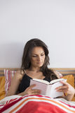 Bello libro di lettura della donna mentre trovandosi a letto a casa Fotografia Stock