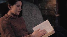 Bello libro di lettura della giovane donna che si siede dal camino in una casa di campagna Chiuda sul concetto del colpo, di fest stock footage