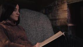 Bello libro di lettura della giovane donna che si siede dal camino in una casa di campagna Chiuda sul concetto del colpo, di fest video d archivio