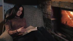 Bello libro di lettura della giovane donna che si siede dal camino in una casa di campagna Chiuda sul concetto del colpo, di fest archivi video