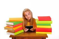 Bello libro elettronico della lettura della ragazza circondato dai libri Fotografia Stock