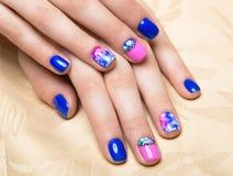 Bello manicure variopinto con le bolle ed i cristalli sulla mano femminile Primo piano Immagini Stock