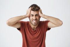 Bello maschio caucasico arrabbiato in maglietta rossa che ha espressioni pazze, schiaccianti testa con le mani orinate della gent Immagini Stock Libere da Diritti