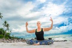 Bello maturi la donna invecchiata che fa l'yoga su un beac tropicale del deserto Fotografie Stock Libere da Diritti