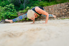 Bello maturi la donna invecchiata che fa l'yoga su un beac tropicale del deserto Fotografia Stock
