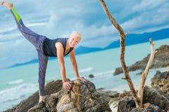 Bello maturi la donna invecchiata che fa l'yoga su un beac tropicale del deserto Immagini Stock Libere da Diritti