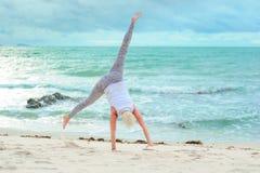 Bello maturi la donna invecchiata che fa l'yoga su un beac tropicale del deserto Immagini Stock
