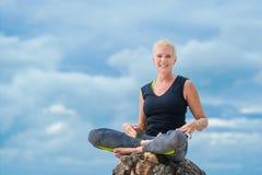 Bello maturi la donna invecchiata che fa l'yoga su un beac tropicale del deserto Fotografie Stock