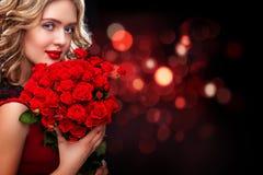 Bello mazzo biondo della tenuta della donna delle rose rosse sul fondo del bokeh Giorno del ` s delle donne del biglietto di S. V Immagine Stock Libera da Diritti