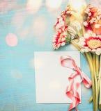 Bello mazzo dei fiori con la cartolina d'auguri, il nastro e il bokeh vuoti su fondo elegante misero blu fotografie stock