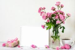 Bello mazzo dei fiori rosa delle rose, della tazza di caffè, dei maccheroni, del contenitore di regalo e della cartolina d'auguri immagine stock