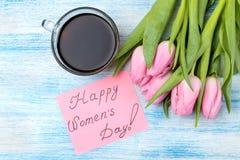 Bello mazzo dei fiori dei tulipani rosa, di una tazza di caffè e del testo del giorno delle donne felici su carta su un backgrou  fotografie stock