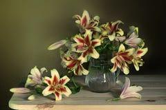 Bello mazzo dei gigli gialli in un vaso su un fondo marrone fotografia stock