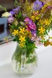 Bello mazzo dei wildflowers in un vaso di vetro Su un fondo del davanzale bianco della finestra Fotografie Stock Libere da Diritti