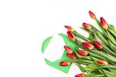 Bello mazzo del tulipano e busta verde con la carta su fondo bianco Fotografia Stock
