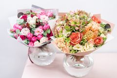 Bello mazzo della molla due disposizioni di fiori con vario dei colori in vaso di vetro sulla tavola rosa Stanza luminosa fotografie stock libere da diritti