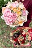 Bello mazzo di estate due Disposizione con i fiori della miscela Ragazza che tiene le disposizioni dei fiori rosse e rosa E fotografia stock