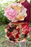 Bello mazzo di estate due Disposizione con i fiori della miscela Ragazza che tiene le disposizioni dei fiori rosse e rosa E immagini stock