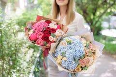 Bello mazzo di estate due Disposizione con i fiori della miscela Ragazza che tiene una disposizione dei fiori con l'ortensia E fotografia stock libera da diritti