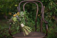 Bello mazzo di nozze dei fiori variopinti su una sedia d'annata sulla natura alla luce di tramonto, decorazioni, preparanti per i Fotografia Stock