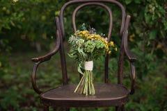 Bello mazzo di nozze dei fiori variopinti su una sedia d'annata sulla natura alla luce di tramonto, decorazioni, preparanti per i Fotografia Stock Libera da Diritti