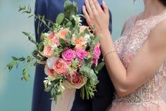 Bello mazzo nuziale in mani della sposa Mazzo di nozze delle rose da David Austin, acqua della pesca della rosa di rosa della uni Fotografia Stock Libera da Diritti