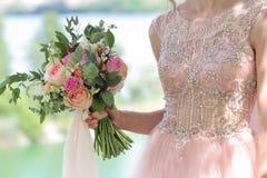 Bello mazzo nuziale in mani della sposa Mazzo di nozze delle rose da David Austin, acqua della pesca della rosa di rosa della uni Immagine Stock