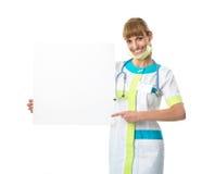 Bello medico della giovane donna che mostra bordo in bianco Immagini Stock