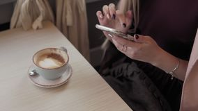 Bello messaggio della ragazza e caffè bevente in caffè della città durante la sua pausa archivi video