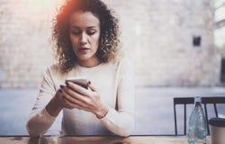 Bello messaggio di posta elettronica affascinante della lettura della giovane donna sul telefono cellulare durante il tempo di re Fotografia Stock Libera da Diritti