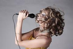 Bello microfono della holding della ragazza. fotografie stock