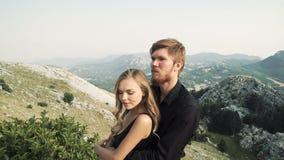 Bello modello amoroso della giovane donna delle coppie in un vestito lungo astuto ed in un uomo in un vestito nero che posa sulla stock footage