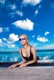 Bello modello biondo della donna con capelli bagnati e trucco elegante che si siedono in uno stagno con le viste stupefacenti in  Fotografia Stock