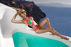 Bello modello biondo femminile con un corpo perfetto e capelli lunghi stupefacenti sull'isola di Santorini in Grecia Fotografia Stock Libera da Diritti