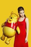 Bello modello con il pallone su fondo giallo Immagine Stock