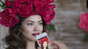 Bello modello, con una corona del color scarlatto delle peonie sulla sua testa Il modello è fotografato sul telefono, uno smartph Fotografia Stock
